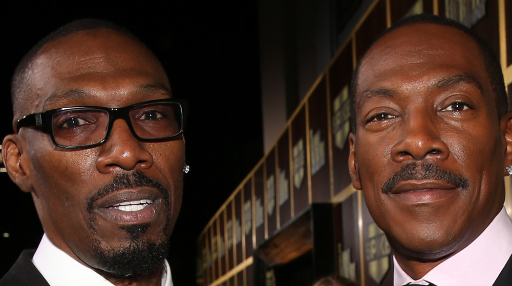 Charlie Murphy in glasses and Eddie Murphy grinning on the red carpet