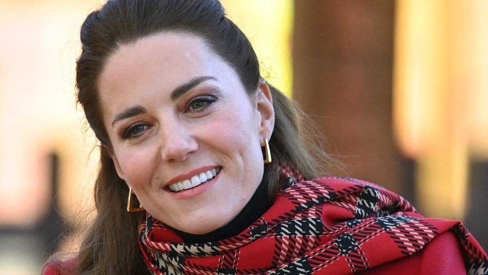 Kate Middleton smiling in a plaid coat