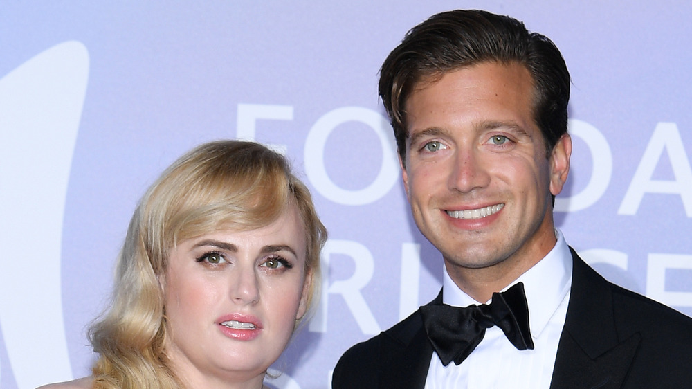 Rebel Wilson, Jacob Busch smiling at formal event