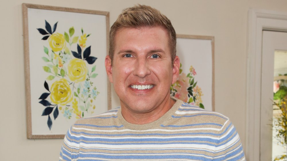 Todd Chrisley in front of paintings of flowers