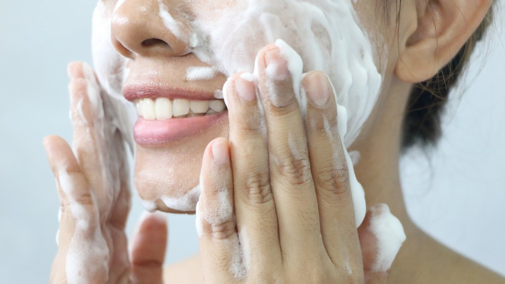 Woman washing her face with lather