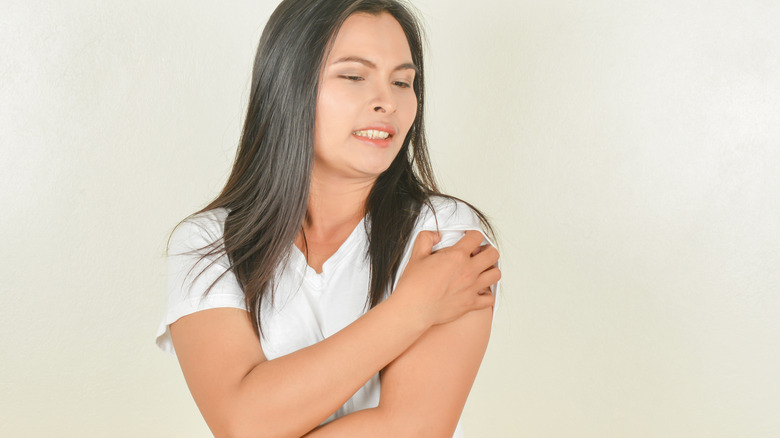 woman with psoriasis scratching arm