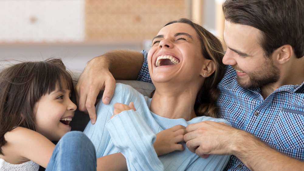 A man, woman, and little girl laughing