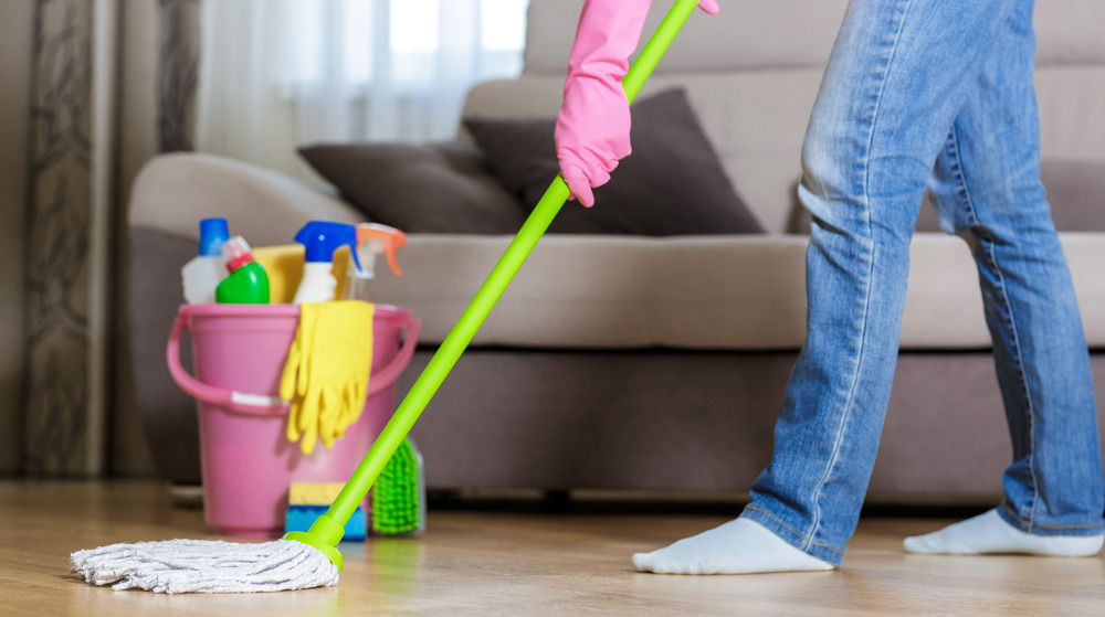 Woman wearing pink gloves mops wood floor in front of a couch.