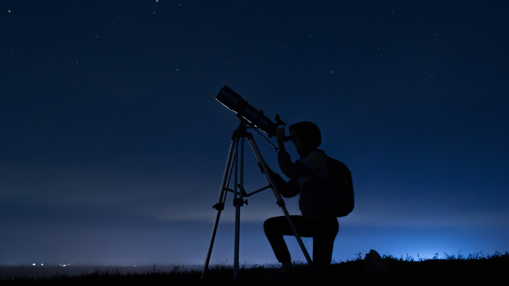 A person looks through a telescope at the night sky