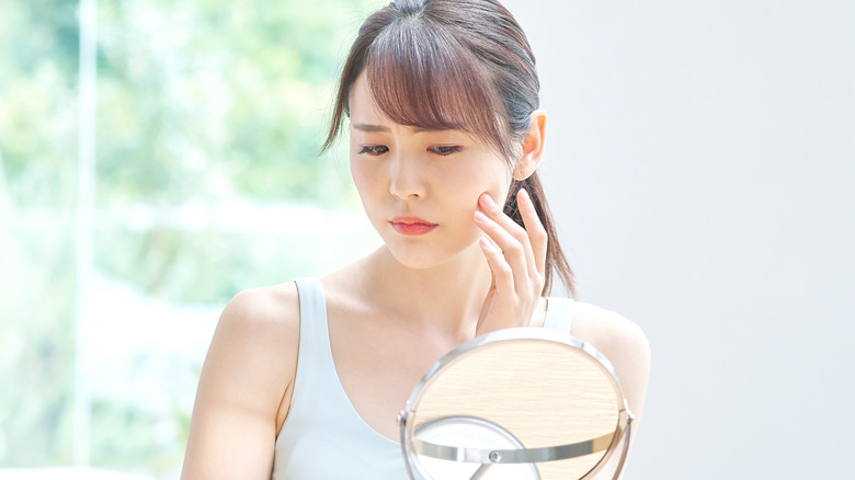 Woman looking at her sallow skin