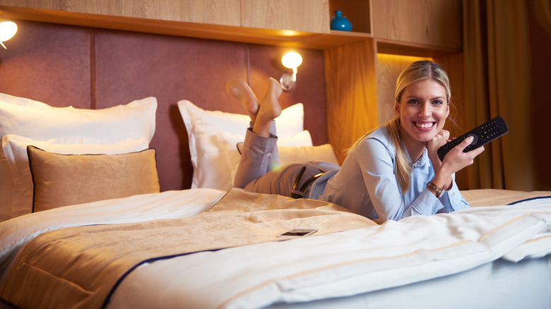 Woman holding remote in hotel room, something you should absolutely avoid touching