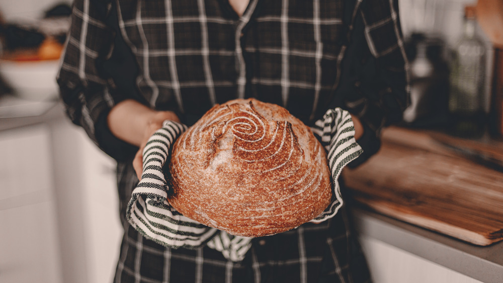 Person holding loaf of bread right out of oven