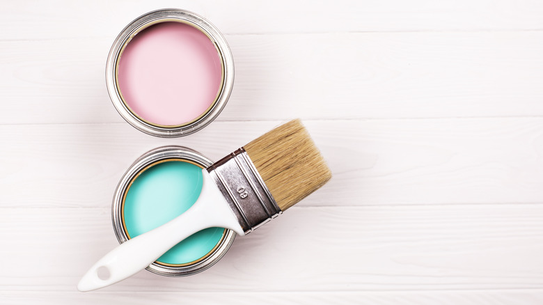 Two paint cans with paintbrush
