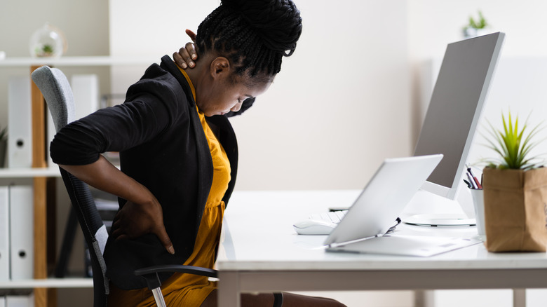 Woman sitting at a desk, experiencing neck and back pain
