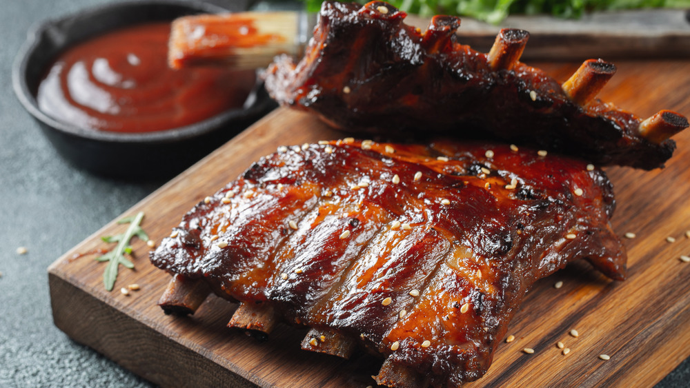 Grilled spare ribs with sauce placed on a wooden cutting board