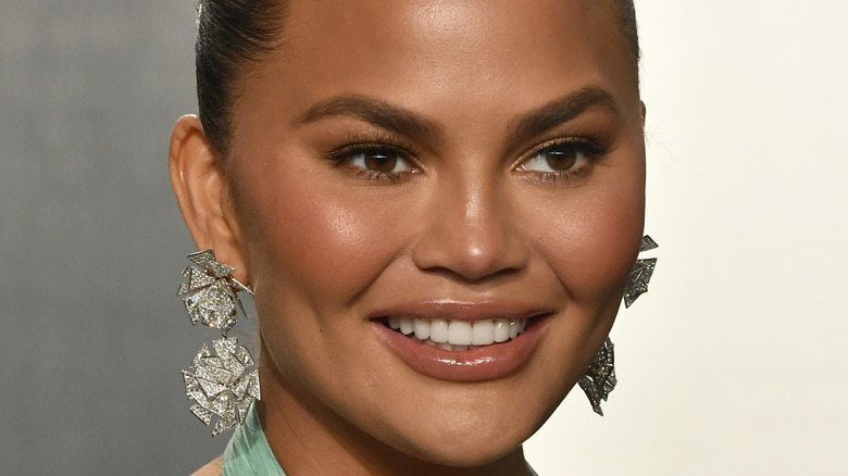 Chrissy Teigen smiling hair back and statement earrings