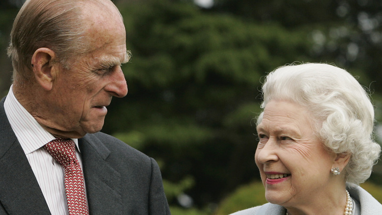 Queen Elizabeth and Prince Philip looking at one another