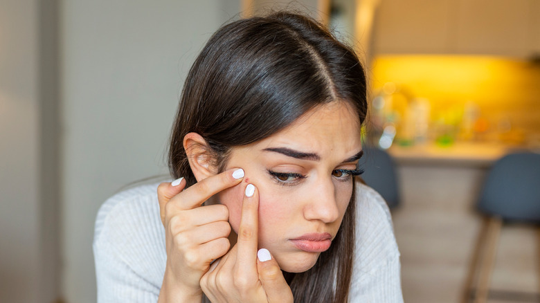 A woman examining a pimple