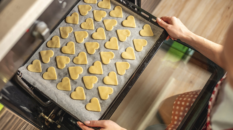 A cookie sheet covered with wax paper and heart shaped cookies