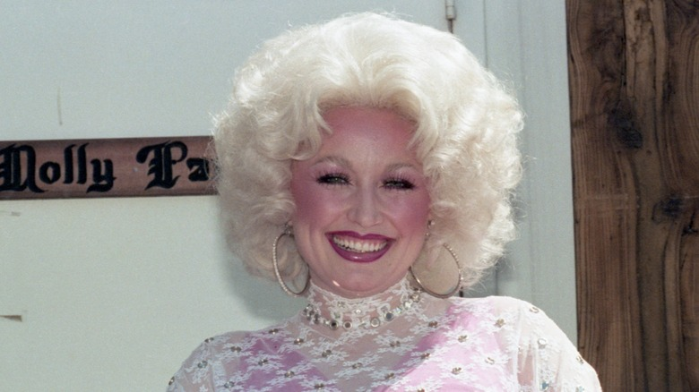 Dolly Parton in the '80s in front of a door