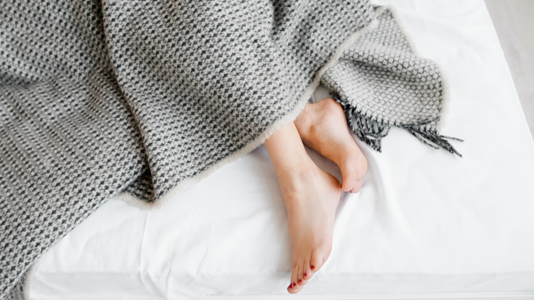 Female feet sticking out from under a blanket on a white linen bed