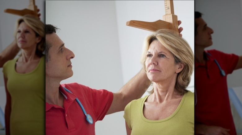 doctor measuring older woman's height