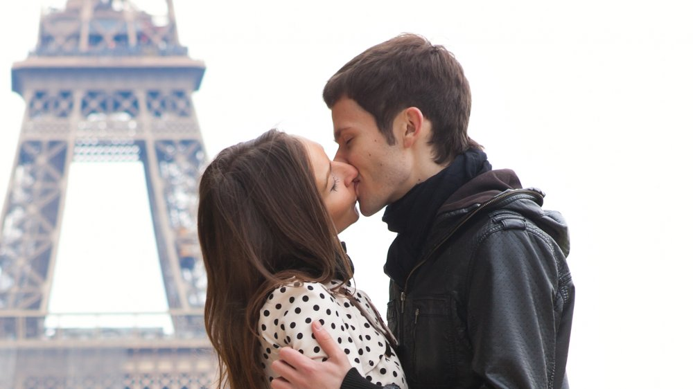 A couple kissing near the Eiffel Tower