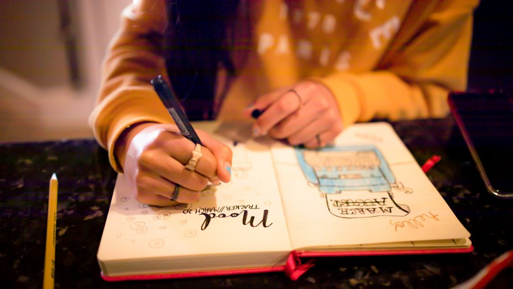 woman's hand writing notes in her journal