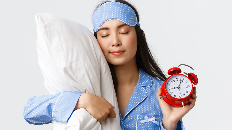 Woman sleeping and dreaming with alarm clock