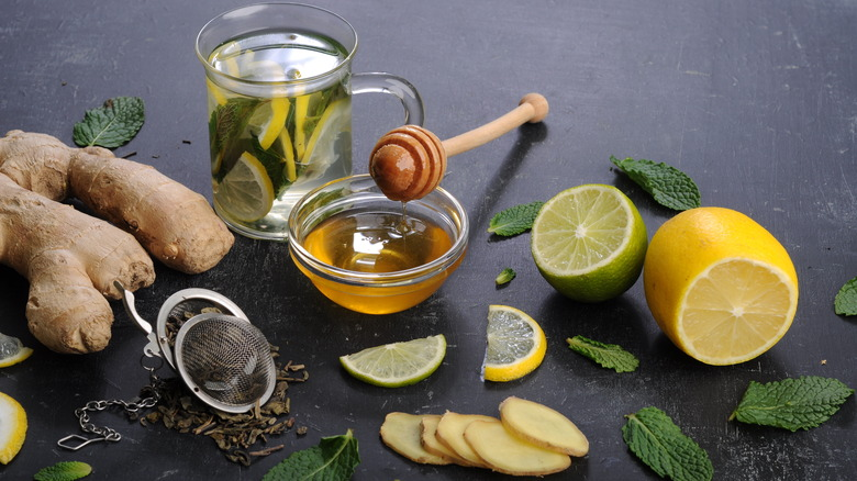 honey surrounded by lemons, ginger, and tea