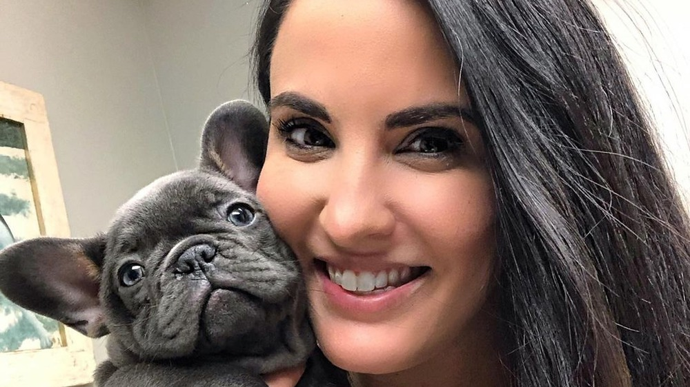 Jackie Duenas poses with a puppy