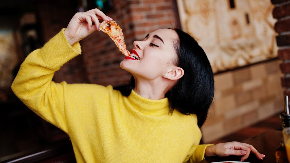 a woman eating a slice of pizza