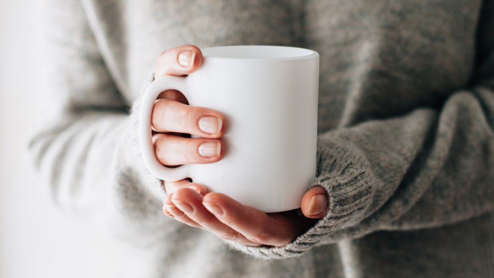 woman holding a mug of hot water