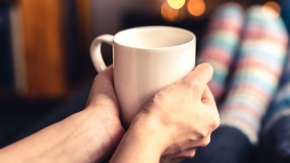 a woman holding a mug of hot water