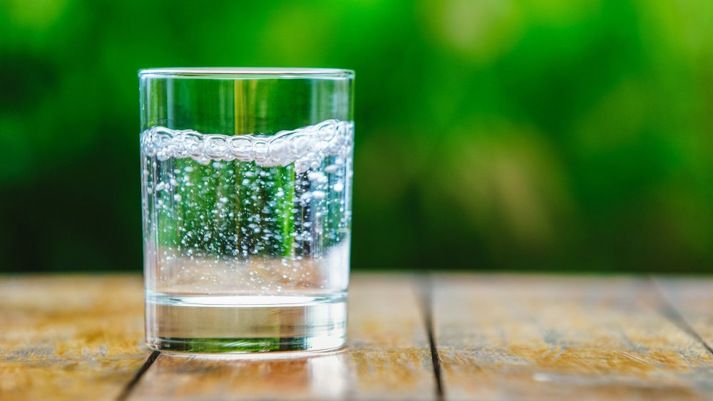 A glass of sparkling water on an outdoor table
