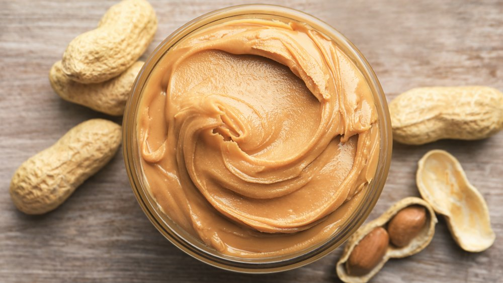 A jar of peanut butter and peanuts from above