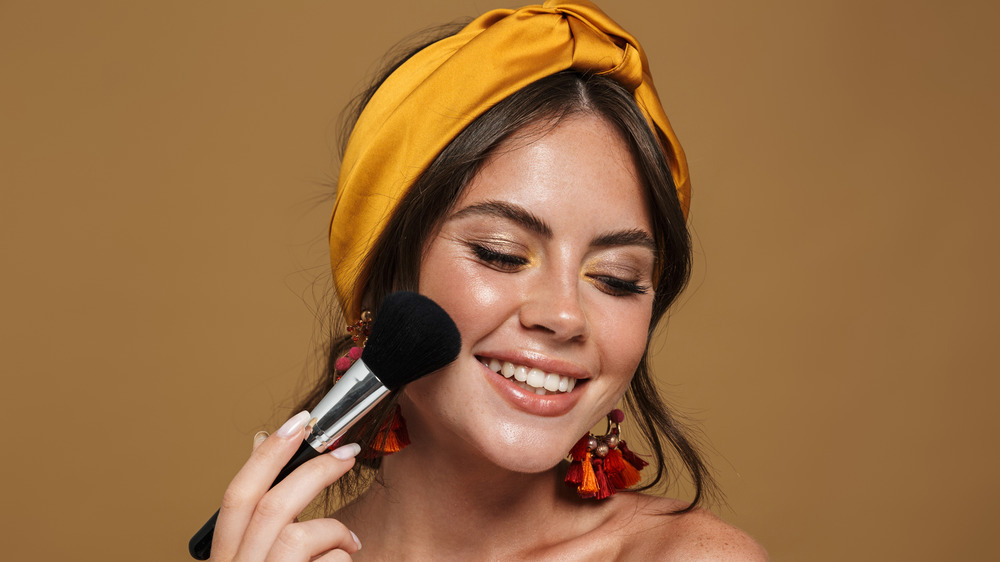 A woman is smiling while applying blush to her face.
