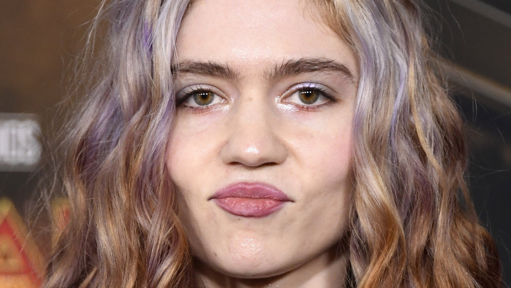 The singer Grimes with pursed lips