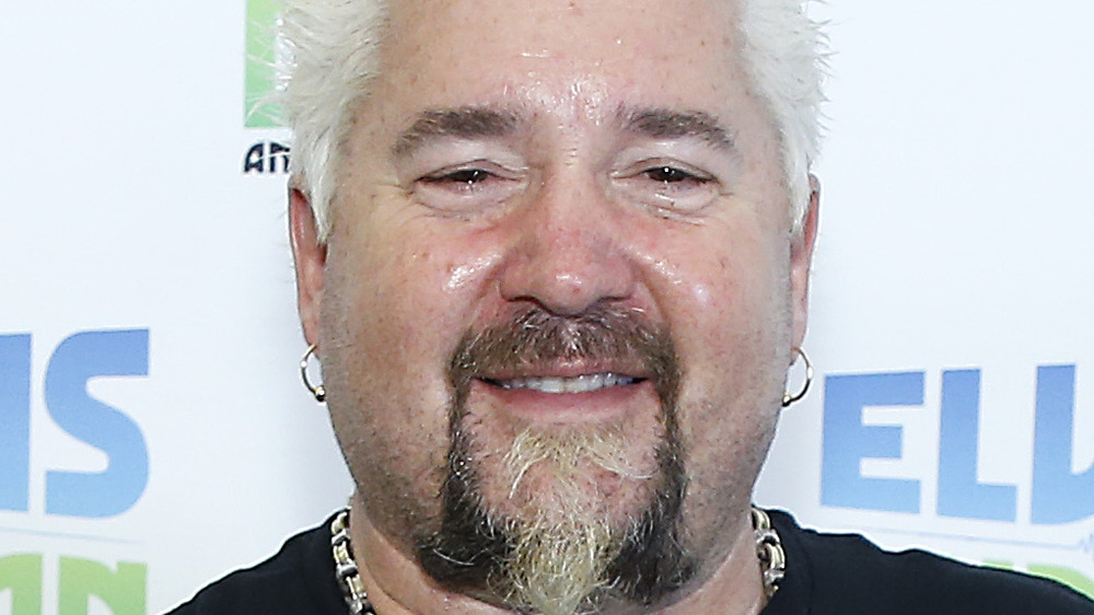 Guy Fieri smiling with earrings and facial hair