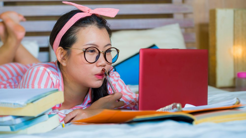 Girl in pajamas remote learning in bed