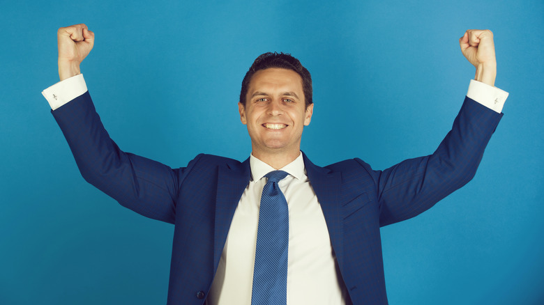 businessman smiling with arms raised